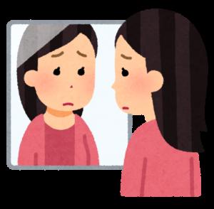 鏡を見る悲しそうな女