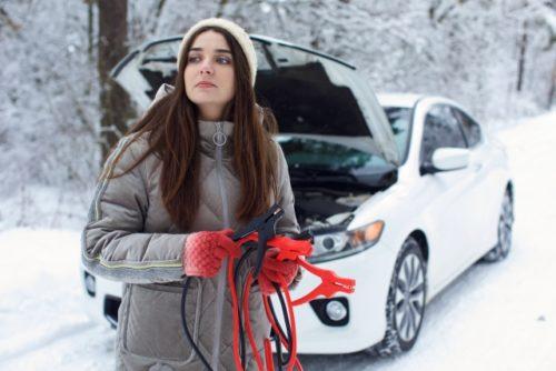 車のバッテリーが上がってしまってジャンプコードを持つ女性